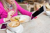 stock photo of internet-cafe  - Woman using tablet computer while having cake and coffee in cafe - JPG