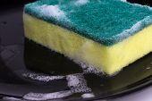 stock photo of dishwasher  - washing dishes with a sponge and dishwashing liquid - JPG