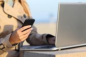 stock photo of self-employment  - Closeup of a self employed woman hand working with a laptop and phone outdoor on the beach - JPG