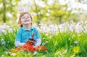 stock photo of bunny ears  - Cute happy little boy wearing Easter bunny ears at spring green grass and blooming apple garden eating chocolate muffing with bunny and having fun outdoors - JPG