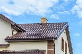 stock photo of downspouts  - chimney on the roof of the house against the blue sky - JPG