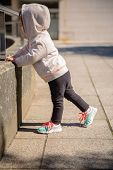 picture of hoodie  - Little girl with sneakers and hoodie warming before training in a city square - JPG