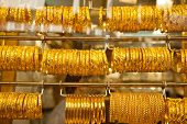 stock photo of dowry  - golden bracelet hanging displayed in the window shop - JPG