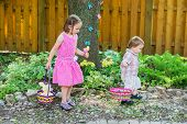 pic of easter basket eggs  - A girl and a little boy holding baskets are having fun searching for colorful eggs on an Easter egg hunt activity outside in a beautiful garden during the spring season - JPG