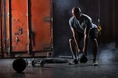 image of studio  - Bald charismatic athlete doing squats with weights - JPG