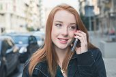 image of redhead  - Beautiful young redhead girl talking on phone in the city streets - JPG