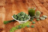 stock photo of chlorella  - Chlorella spirulina and wheat grass pills ground powder on wooden background - JPG