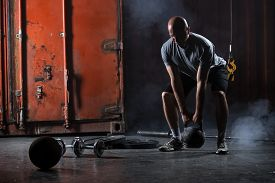 picture of studio  - Bald charismatic athlete doing squats with weights - JPG