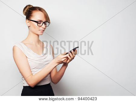 Business, finance and people concept: beautiful young businesswoman holding mobile phone, standing against grey background