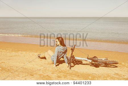 Girl With A Bike Sitting On Beach
