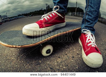 Rider with red shoes standing on the asphalt road with skate board