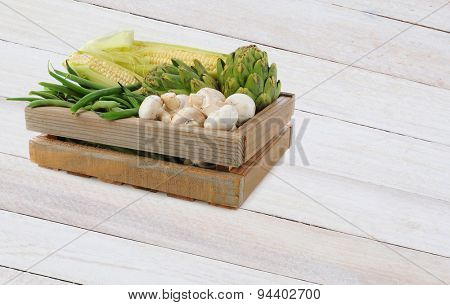 A wood crate fill with assorted vegetables on a rustic wood table. Mushrooms, Corn, Artichokes and Green Beans fill the box.