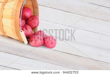 High angle shot of a basket full of red potatoes spilling onto a rustic wood table. horizontal format with copy space.