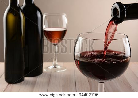 Closeup of a glass of wine and a bottle pouring. Out of focus wine bottles and another wineglass are in the background. Horizontal still life with warm tones and light to dark background lighting.