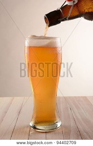 Beer pouring into a tall glass from a swing top bottle. On a wood table with a light ot dark background.
