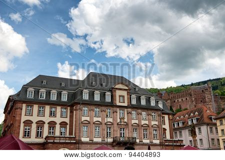 Facade of Historic Town Hall with View of Heidelberg Castle in Background, Framed by Blue Sky with Heavy Clouds, Heidelberg, Baden-Wurttemberg, Germany