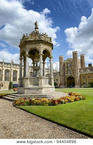 Historical fountain in the Great Court,Trinity College, Cambridge University, Cambridge, UK with a view of the Great Gate behind