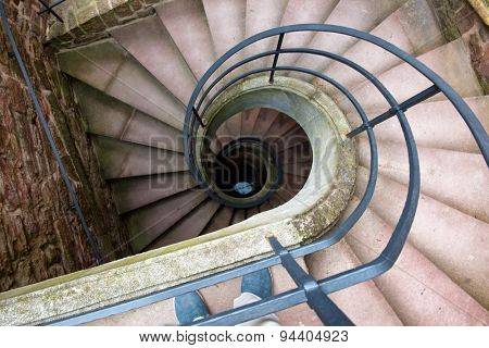 High Angle View of Spiral Staircase Winding Downward in Historical Building, Looking Down at Bottom of Stairs in Elegant Old Building