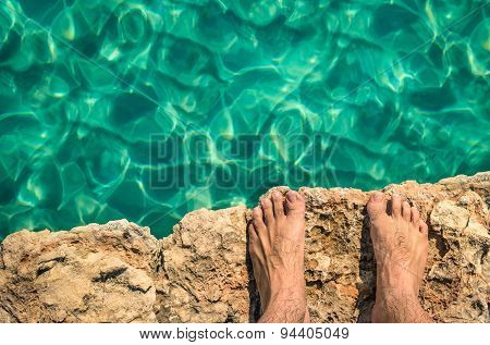 Naked Human Barefoot On Rock Cliff Ready To Jump In The Clear Blue Water - Gozo Blue Lagoon