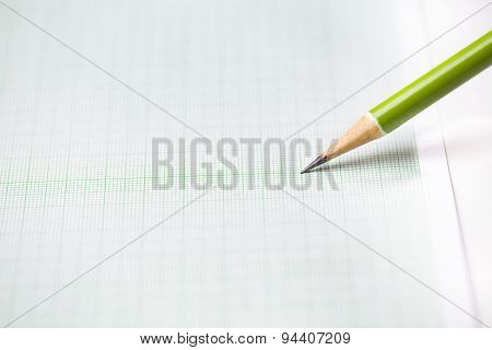 Close-up Green Pencil On Graph Paper Background