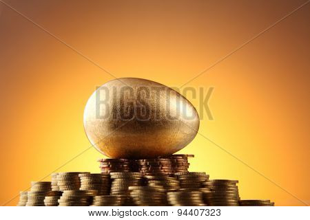 golden egg rest on stacks of coins