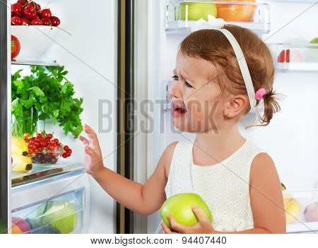 Little Girl Child Is Crying And Acting About Fridge With Fruit