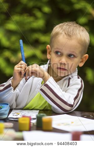 Little boy thinking with a pencil while drawing.