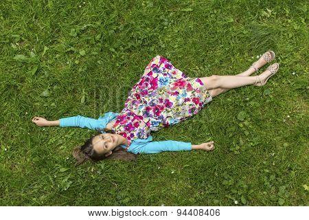 Cute little girl lying on green grass (top view)