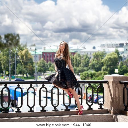 Portrait in full growth, Young beautiful brunette woman in black dress posing outdoors in sunny weather