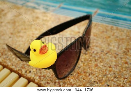Sunglasses With Yellow Rubber Duck At The Swimming Pool.