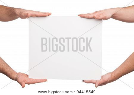 four hands holding a blank white board