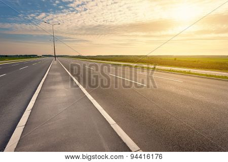Driving On An Empty Motorway Towards The Setting Sun