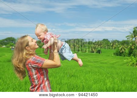 On Green Rice Terraces Background Mother Tossing Joyful Baby Boy