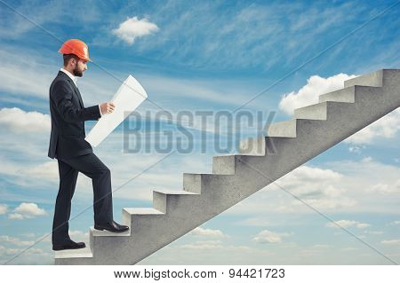businessman in orange hardhat holding blueprint and following up on concrete stairs over blue sky