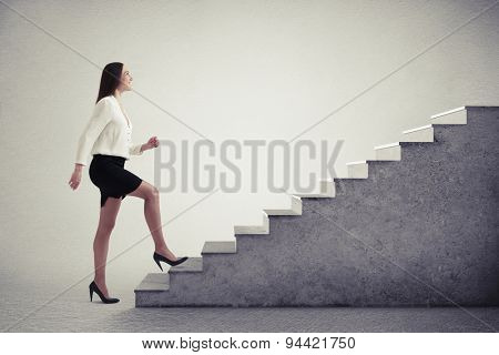 smiley businesswoman in formal wear walking up stairs over light grey background