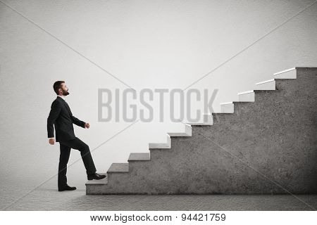 smiley businessman in formal wear walking up stairs over light grey background