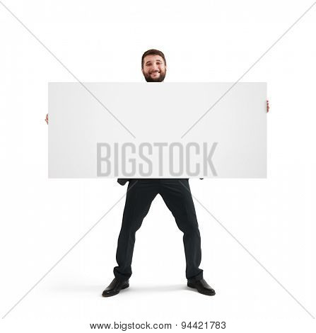 smiley businessman holding empty banner and looking at camera. isolated on white background