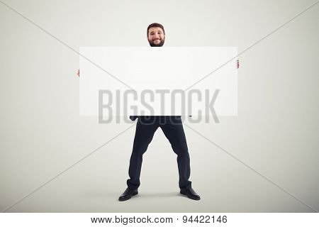 smiley businessman holding empty banner and looking at camera over grey background