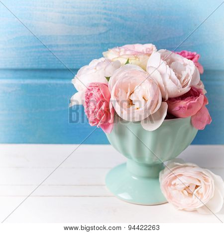 Pastel Roses In Turquoise Vase On White Wooden  Background