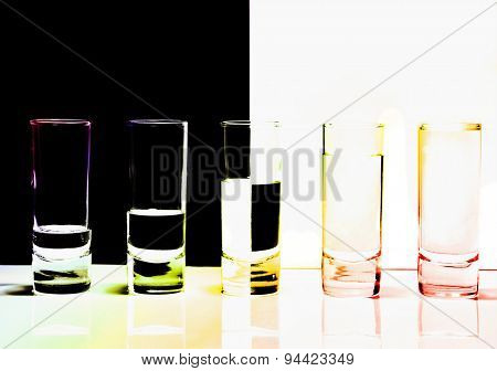 A row of glasses for vodka in color lights on black&white background