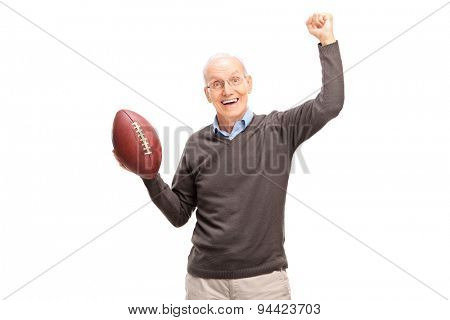 Studio shot of a joyful senior man holding an American football and gesturing happiness isolated on white background