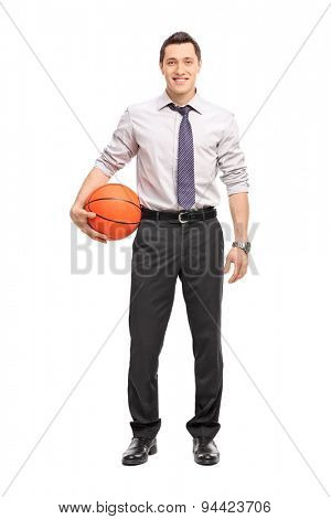 Full length portrait of a handsome businessman holding a basketball isolated on white background