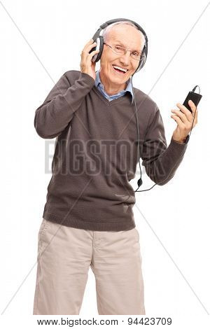 Vertical shot of a happy senior listening to music on headphones from his cell phone isolated on white background