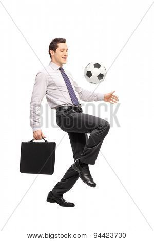Full length portrait of a young businessman holding a briefcase and juggling a football isolated on white background
