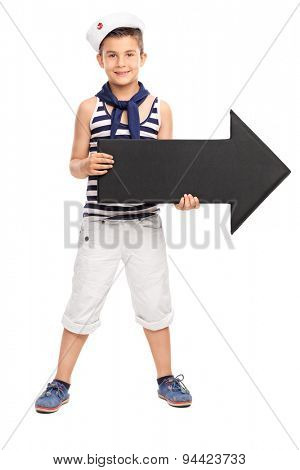 Full length portrait of a little boy in sailor outfit holding a big black arrow pointing right isolated on white background