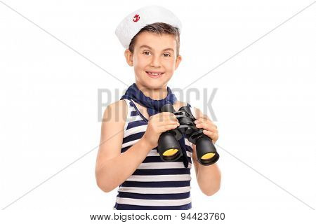 Joyful little boy in a sailor outfit holding a pair of binoculars and looking at the camera isolated on white background