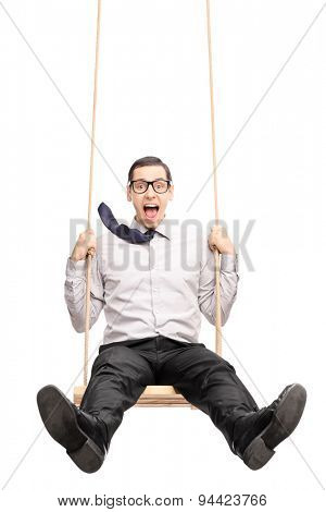 Vertical shot of a joyful young guy swinging fast on a wooden swing isolated on white background
