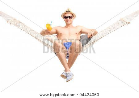Carefree young guy sitting in a comfortable hammock and drinking an orange cocktail isolated on white background