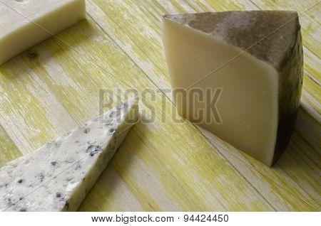 Spanish Manchego Cheese, Gruyere, Gorgonzola Over Yellow Wood.