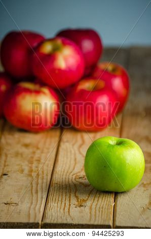 Green apple over red apples